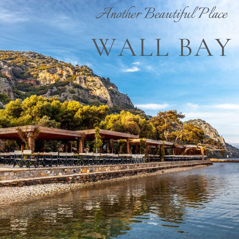Wall Bay, like everywhere in this area is surrounded by forested hills, but the layout of the terrain, sharp rock wall and beautiful colors of water make an impression from the very first moment when we came in to it.  The restaurant, which stands in this place with its architecture and arranged area, with bathrooms, library and gallery will satisfy the appetite of the most sophisticated aesthete. Stone walkways surrounded by lavenders, wooden pergolas overgrown with vines, fields of flowering bananas and flower beds. Olive trees, clay pitchers .... and right in the middle of this charming place, a modern library / gallery with many albums over which you can spend hours, sanitary facilities in a great modern artistic style and a shop that can be part of high street. All this is additionally embellished with small decorations hung on the trees.  Place definitely recommendable.